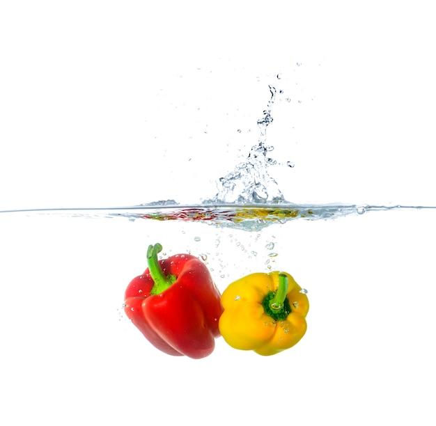 Respingo de pimentão vermelho e amarelo fresco na água Foto Premium