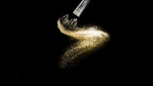 Respingo de pó dourado e pincel para maquiador ou blogger de beleza em fundo preto Foto Premium