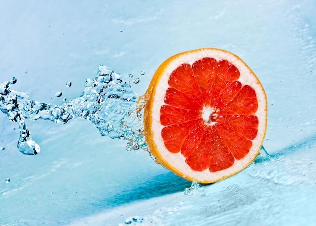 Respingos de água doce na toranja vermelha Foto Premium