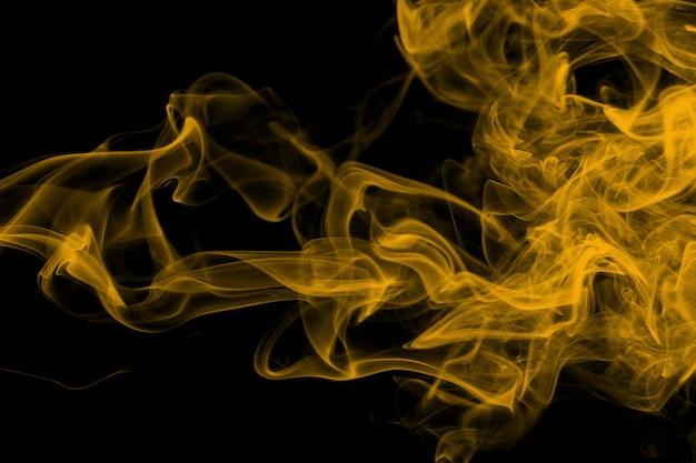 Resumo de fumaça amarela sobre fundo preto, fogo Foto Premium