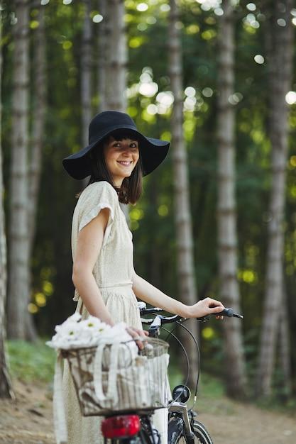 Retrato ao ar livre de atraente jovem morena de chapéu em uma bicicleta. Foto gratuita