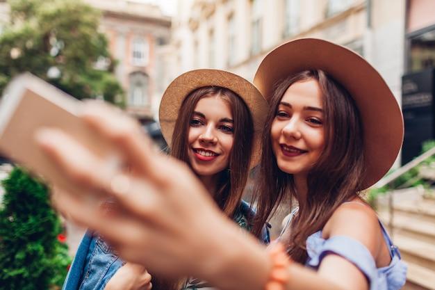 Retrato ao ar livre de duas mulheres bonitas novas que tomam o selfie usando o telefone. garotas se divertindo na cidade. melhores amigos Foto Premium