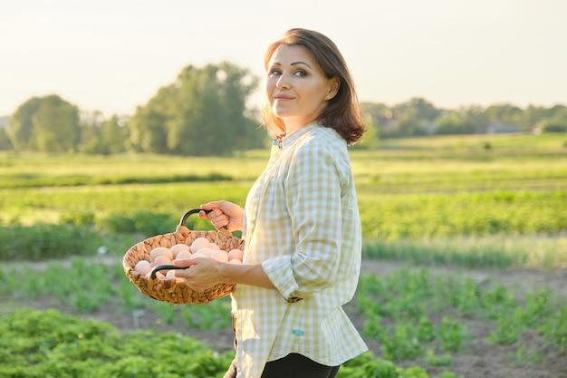 Retrato ao ar livre de mulher de fazendeiro com cesta de ovos de galinha fresca, fazenda Foto Premium