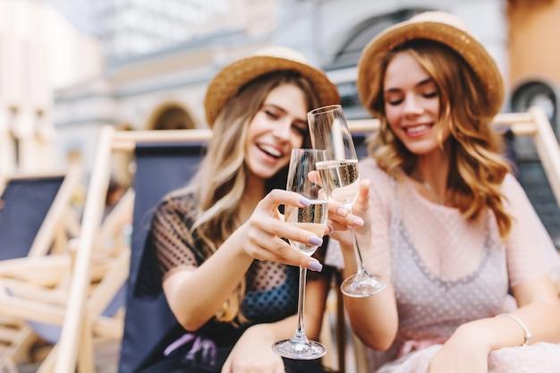 Retrato ao ar livre de mulheres jovens e alegres celebrando as férias com taças de champanhe em primeiro plano Foto gratuita