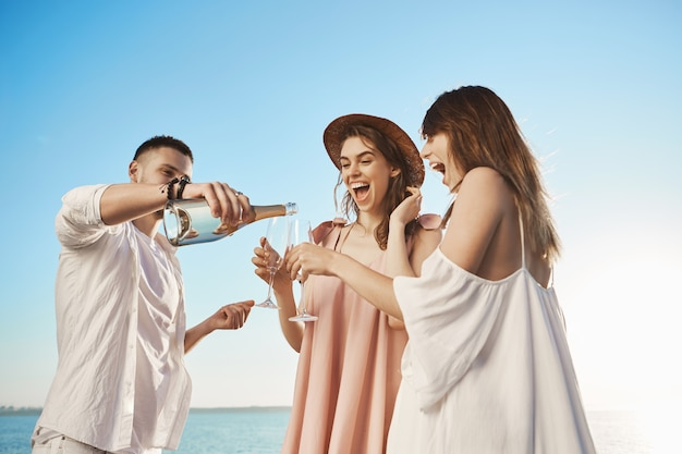Retrato ao ar livre de três jovens adultos, bebendo champanhe e sorrindo amplamente enquanto descansava à beira-mar. o cara barbudo bonitão bebe para os óculos de seus amigos, dizendo um brinde ao seu futuro feliz Foto gratuita