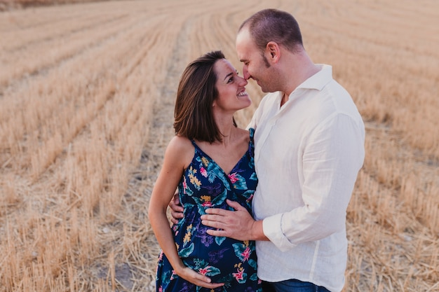 Retrato ao ar livre de um jovem casal grávida em um campo amarelo. estilo de vida familiar ao ar livre. Foto Premium