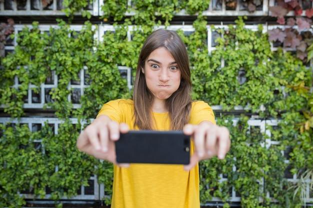 Retrato ao ar livre de uma bela jovem, tirando uma foto com o celular e fazendo uma cara engraçada. vestindo uma camisa casual amarela e sorrindo. Foto Premium