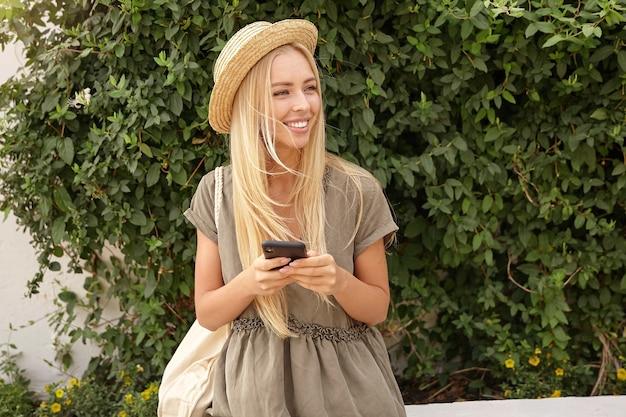 Retrato ao ar livre de uma linda jovem loira com um vestido de linho casual sobre um jardim verde, mantendo o smartphone nas mãos e olhando para o lado com um largo sorriso Foto gratuita
