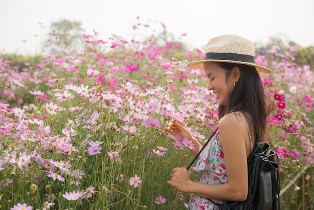 Retrato ao ar livre de uma mulher envelhecida média bonita de ásia. garota atraente em um campo com flores Foto gratuita