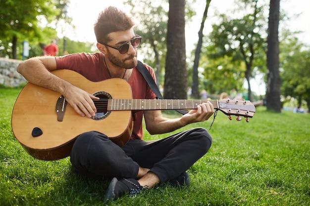 Retrato ao ar livre do cara bonito hipster sentado na grama do parque tocando violão Foto gratuita