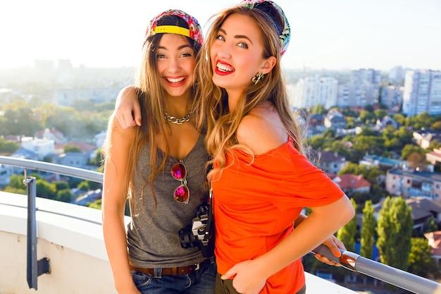 Retrato ao ar livre do estilo de vida das duas melhores irmãs do demônio posando no telhado Foto gratuita