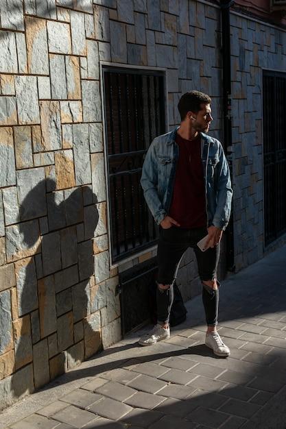Retrato ao ar livre do homem novo moderno com o telefone esperto na rua. Foto Premium