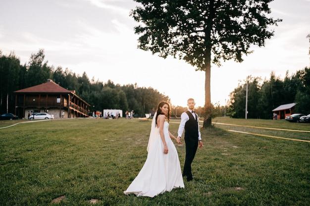 Retrato ao ar livre lindo casal de noivos. noiva bonita nova que abraça o noivo no por do sol contra o encapement Foto Premium