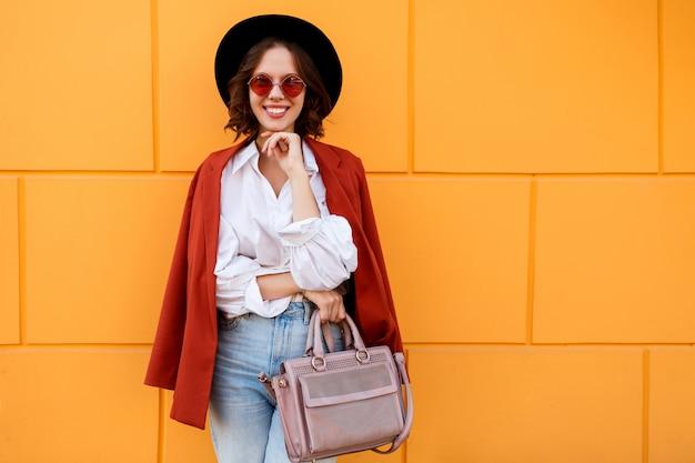 Retrato ascendente próximo ao ar livre da fêmea de cabelos curtos moreno feliz que levanta sobre a parede amarela. chapéu da moda, óculos cor de rosa, blusa branca e calça jeans. Foto gratuita