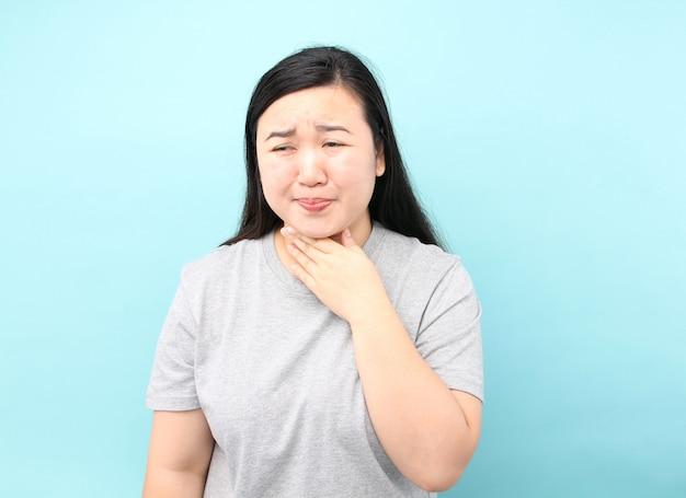 Retrato ásia mulher há uma dor de garganta, sobre fundo azul no estúdio. Foto Premium