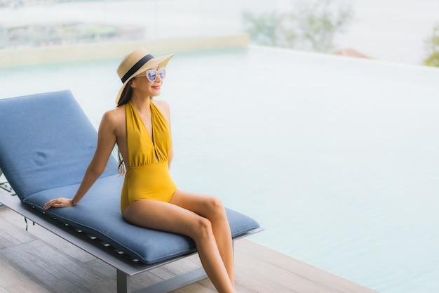 Retrato asiático bela jovem feliz sorriso relaxar ao redor da piscina em férias Foto gratuita