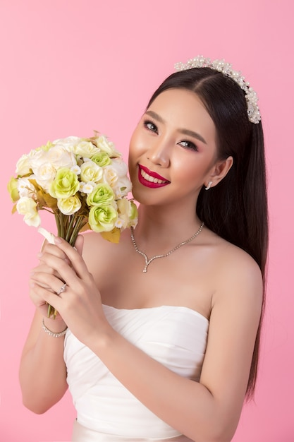 Retrato asiático bonito da noiva no estúdio cor-de-rosa Foto gratuita