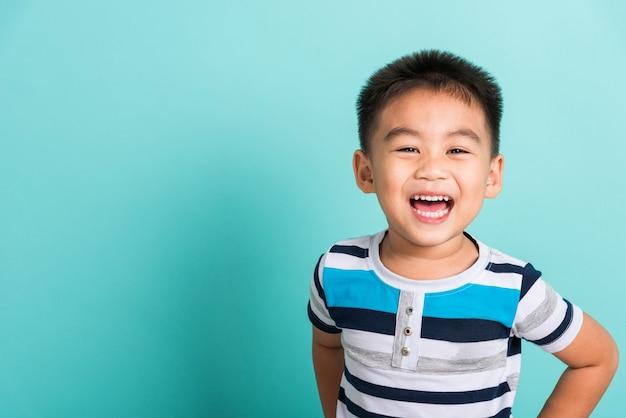 Retrato asiático de um menino feliz, ele rindo, sorrindo e olhando para a câmera Foto Premium