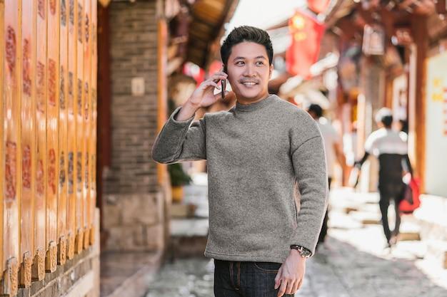 Retrato asiático felicidade homem usando telefone celular inteligente para ligar Foto Premium