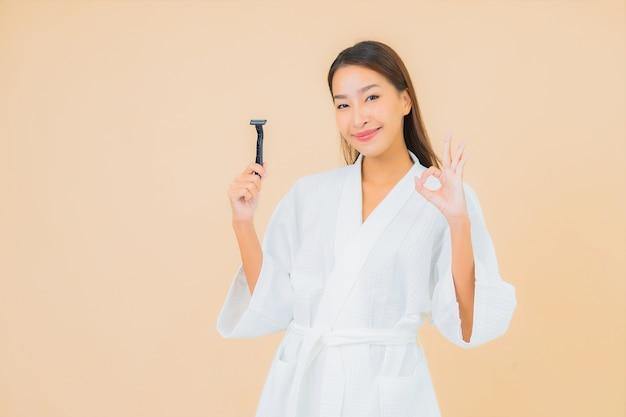 Retrato bela jovem asiática com barbear na cor bege Foto gratuita