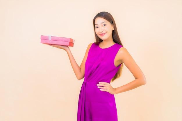 Retrato bela jovem asiática com caixa de presente vermelha em fundo de cor isolada Foto gratuita