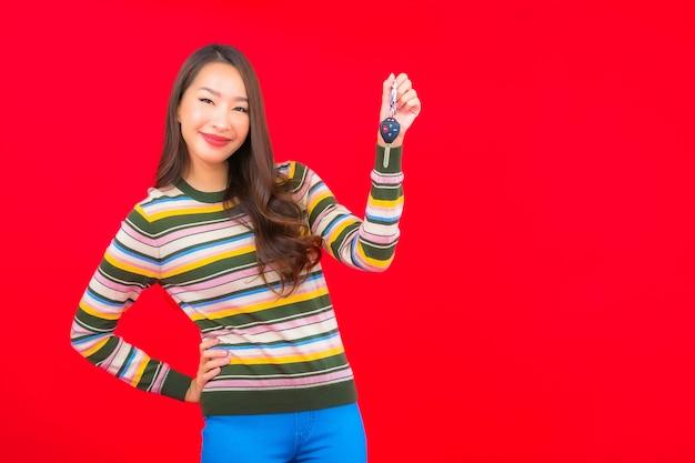 Retrato bela jovem asiática com chave do carro na parede vermelha isolada Foto gratuita
