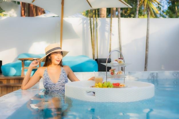 Retrato bela jovem asiática desfrutar com chá da tarde ou café da manhã flutuando na piscina Foto gratuita