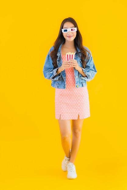 Retrato bela jovem asiática desfrutar feliz com pipoca e assistir filme Foto gratuita