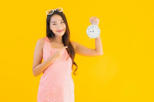Retrato bela jovem asiática mostrar alarme ou relógio Foto gratuita