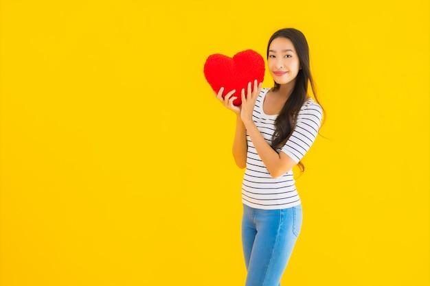 Retrato bela jovem asiática mostrar almofada de coração Foto gratuita