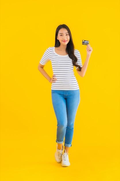 Retrato bela jovem asiática mostrar cartão de crédito Foto gratuita