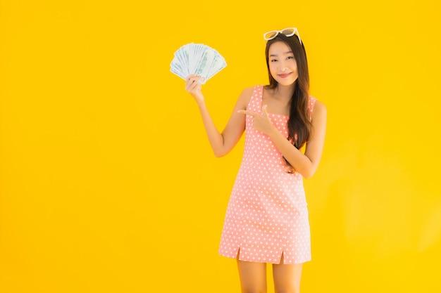 Retrato bela jovem asiática mostrar muito dinheiro e dinheiro Foto gratuita