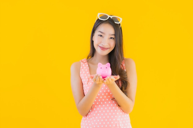 Retrato bela jovem asiática mostrar muito dinheiro ou dinheiro com mealheiro Foto gratuita