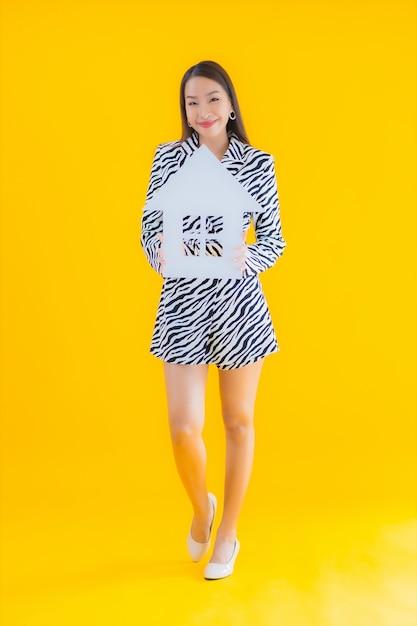 Retrato bela jovem asiática mostrar sinal de casa ou casa em amarelo Foto gratuita