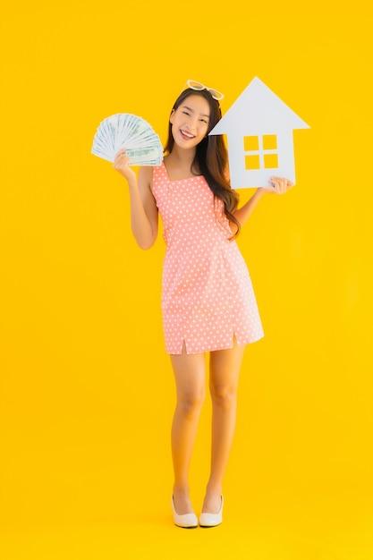 Retrato bela jovem asiática mostrar sinal de casa ou casa Foto gratuita