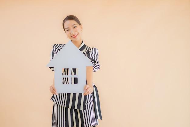 Retrato bela jovem asiática mostrar sinal de papel em casa ou casa Foto gratuita
