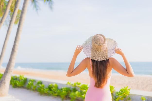 Retrato bela jovem asiática relaxando lazer ao redor da piscina ao ar livre com o mar Foto gratuita