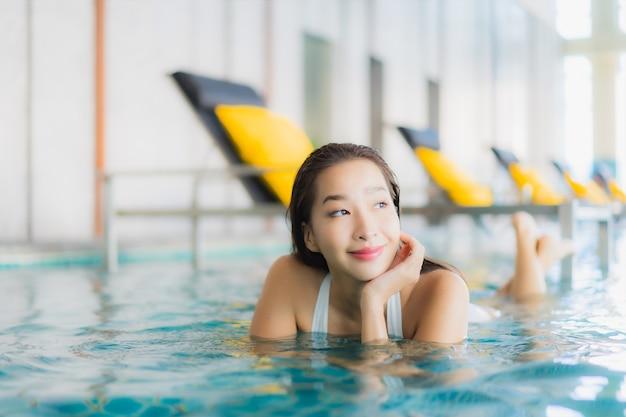 Retrato bela jovem asiática relaxando sorriso ao redor da piscina em hotel resort em traval férias Foto gratuita