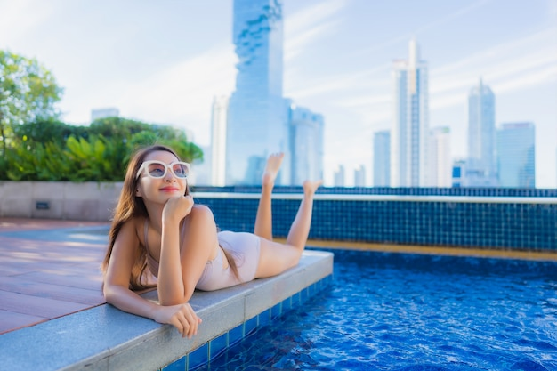 Retrato bela jovem asiática relaxar lazer desfrutar em torno da piscina ao ar livre Foto gratuita