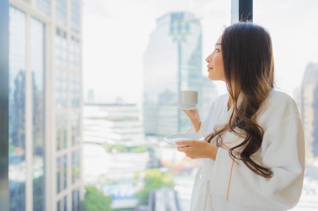 Retrato bela jovem asiática segurar a xícara de café com vista cidade Foto gratuita