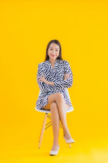 Retrato bela jovem asiática sentar na cadeira com ação em amarelo Foto gratuita