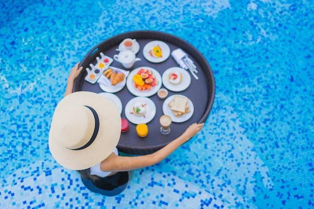 Retrato bela jovem asiática sorriso feliz com pequeno-almoço flutuante na bandeja na piscina Foto gratuita