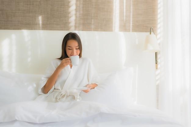 Retrato bela jovem asiática sorriso feliz com uma xícara de café na cama Foto gratuita