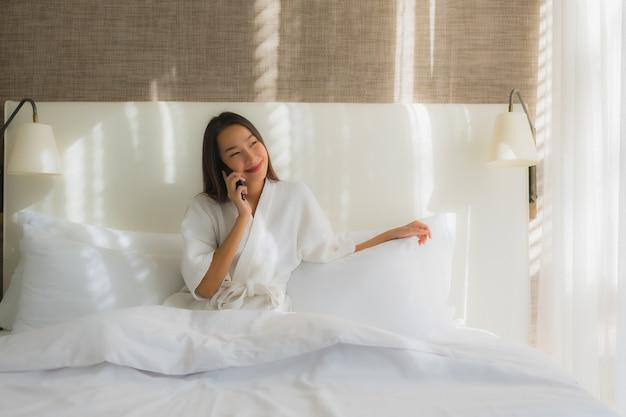 Retrato bela jovem asiática usando telefone celular inteligente na cama no quarto Foto gratuita