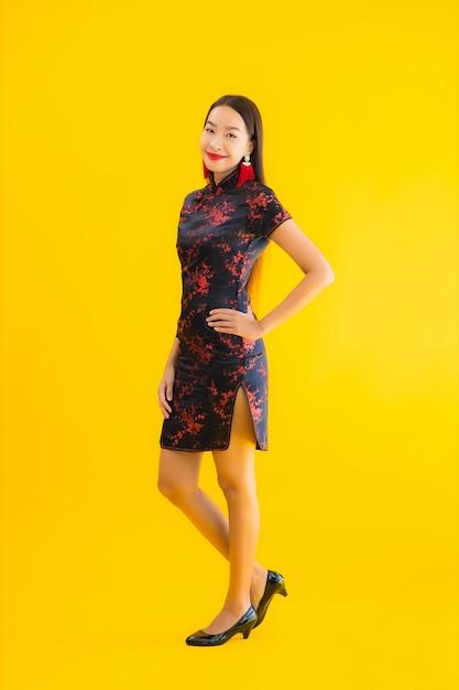 Retrato bela jovem asiática usar vestido chinês com ação Foto gratuita