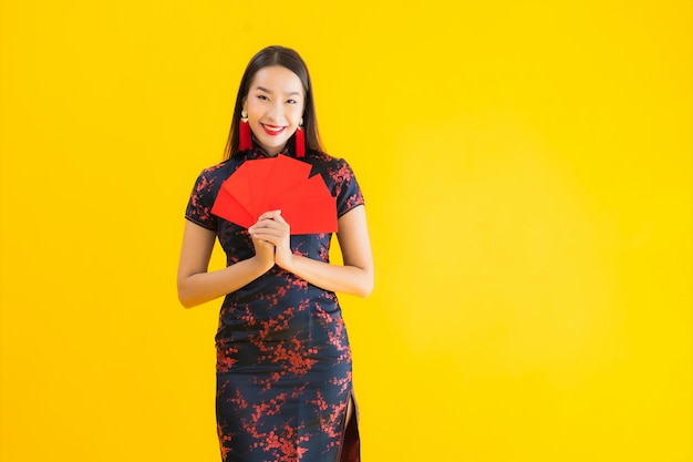 Retrato bela jovem asiática usar vestido chinês com ang pao ou letra vermelha com dinheiro Foto gratuita