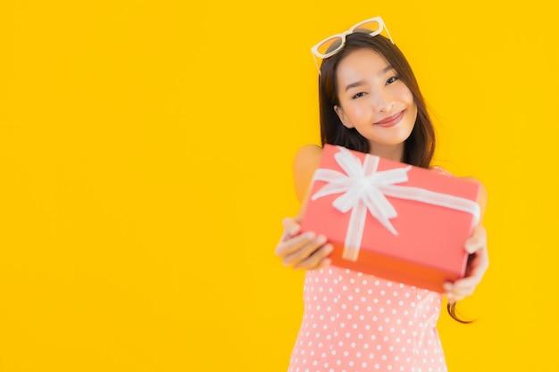 Retrato bela jovem mulher asiática com caixa de presente vermelha Foto gratuita