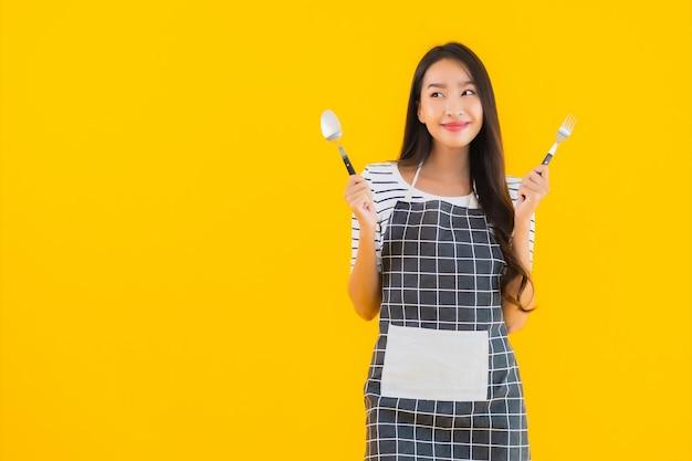 Retrato bela jovem mulher asiática com colher e garfo Foto gratuita