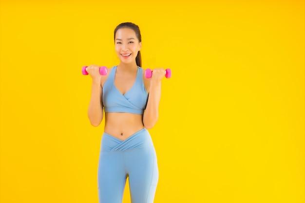 Retrato bela jovem mulher asiática com halteres e sportwear amarelo Foto gratuita