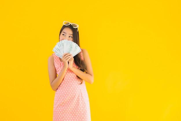 Retrato bela jovem mulher asiática com muito dinheiro Foto gratuita